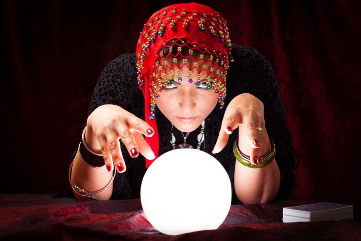 Portrait Of Mysterious Fortune Teller Gesturing At Crystal Ball
